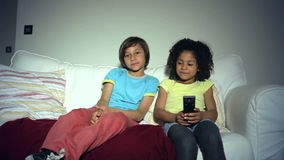 Two African American Children On Sofa Arguing Over TV Remote. Two children sitting on sofa disagreeing about what to watch on tv .Shot on Canon 5d Mk2 with a stock video