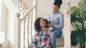 Two african american curly girls sistres make fun curly hairstyle each other and have fun at home. Two african american curly girls sistres make fun curly stock footage