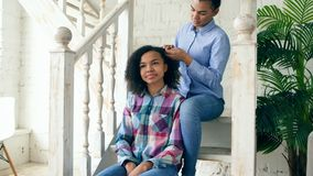 Two african american curly girls sistres make fun curly hairstyle each other and have fun at home stock photos