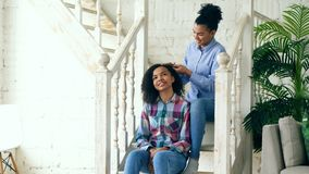 Two african american curly girls sistres make fun curly hairstyle each other and have fun at home stock photo