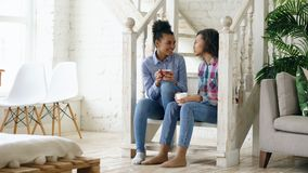 Two african american curly girls sistres sitting on stairs have fun laughing and chatting together at home. Two african american curly girls sistres sitting on Stock Images