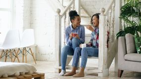 Two african american curly girls sistres sitting on stairs have fun laughing and chatting together at home. Two african american curly girls sistres sitting on stock photo