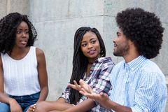 Two african american women talking with friend from Africa Stock Images