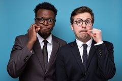 Free Two African And Caucasian Men Shut Mouth As Zip With Fingers Stock Images - 208250204
