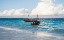 Two african boats near the shore with beautiful sea and sky on the background Stock Photos