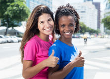 Two african and caucasian women showing thumb in the city Royalty Free Stock Images