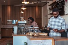 Two African entrepreneurs busy working at their cafe counter Stock Photos