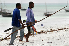 Two African fisherman divers carry home caught fish. Royalty Free Stock Photos