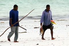 Two African fisherman divers return home with their catch. Royalty Free Stock Image