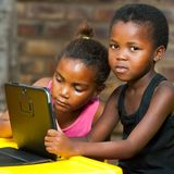 Two african girls sitting at table with tablet. stock images