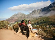 Two african guys sitting on a bench with a view