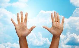 Two african hands making high five over blue sky Stock Photos