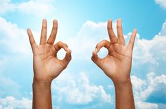 Two african hands showing ok sign over blue sky. Gesture, people and body parts concept - african woman two hands showing ok sign over blue sky and clouds Royalty Free Stock Photography