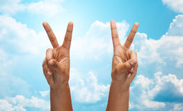 Two african hands showing victory or peace sign. Gesture, people and body parts concept - african woman two hands showing victory or peace over blue sky and Stock Photography
