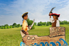 Two African kids as pirates dueling with swords. Two African kids, boy and girl dressed as pirates dueling with swords on ship against each other royalty free stock photos