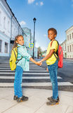 Two African kids hold hands, stand near crossroad. Two African kids holding hands and standing near crossroad and smile in city during summer stock photos
