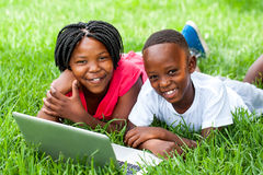 Two african kids laying on grass with laptop. Close up portrait of cute African kids laying on grass with laptop stock photography