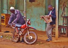 Two African Men, One Reading the Newpaper and One Perparing His Motorcyle. A day in the life of this small town is reflected by the two men in this picture. One stock image