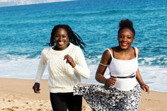 Two african teen girls running on beach. Stock Images