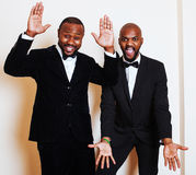 Two afro-american businessmen in black suits emotional posing, g Royalty Free Stock Images