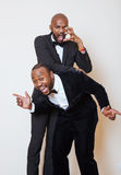 Two afro-american businessmen in black suits emotional posing, gesturing, smiling. wearing bow-ties. Close up Stock Photography