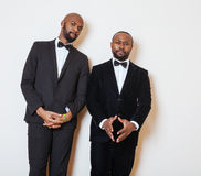Two afro-american businessmen in black suits emotional posing, gesturing, smiling. wearing bow-ties. Close up Stock Images