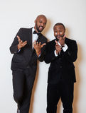Two afro-american businessmen in black suits emotional posing, gesturing, smiling. wearing bow-ties. Close up Royalty Free Stock Photo