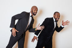 Two afro-american businessmen in black suits emotional posing, gesturing, smiling. wearing bow-ties Stock Photo