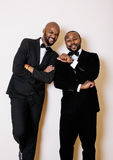 Two afro-american businessmen in black suits emotional posing, gesturing, smiling. wearing bow-ties. Close up Royalty Free Stock Photos