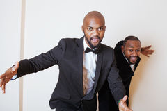 Two afro-american businessmen in black suits emotional posing, gesturing, smiling. wearing bow-ties. Close up Stock Image