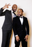 Two afro-american businessmen in black suits emotional posing, gesturing, smiling. wearing bow-ties. Close up Stock Photo