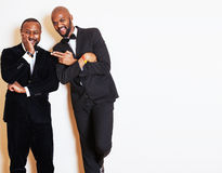 Two afro-american businessmen in black suits emotional posing, gesturing, smiling. wearing bow-ties Royalty Free Stock Photography