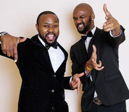 Two afro-american businessmen in black suits emotional posing, gesturing, smiling. wearing bow-ties Stock Image