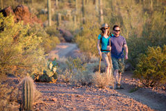 Two Afternoon Hikers on Rugged Desert Trail Stock Photography