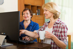 Two aged collegues with PC. Two aged colleagues looking at PC screen and smiling with cup of coffee in hands Stock Photos