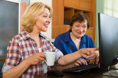 Two aged collegues with PC. Two aged colleagues looking at PC screen and smiling with cup of tea in hands Royalty Free Stock Photos