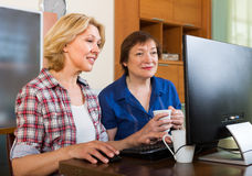 Two aged collegues with PC. Two smiling elderly women looking at PC screen with cup of tea in hands Royalty Free Stock Photography
