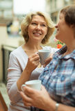 Two aged housewives enjoying tea at terrace. With decorative plants Stock Image