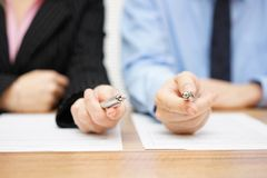Two agents giving his client a pen to sign a deal Stock Photo
