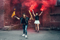 Two aggressive women with Molotov cocktail bomb in the street. Two aggressive women with Molotov cocktail and red smoke bomb in the street.  Outdoor lifestyle Stock Image