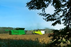 Two agricultural machines operate in the field, grain harvesting machines operate in the field, agricultural land. Agricultural land, ain harvesting machines Stock Photography