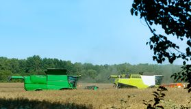 Two agricultural machines operate in the field, grain harvesting machines operate in the field, agricultural land. Agricultural land, ain harvesting machines Royalty Free Stock Photography
