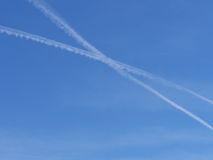 Two airplane con trails cross in the blue sky Stock Photography