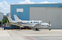 Two airplanes. Two turboprop airplanes parked in front of hangar stock photography