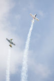 Two airplanes doing stunt. Two of old style aerobatic sport airplanes doing stunt with smoke trails Royalty Free Stock Photo