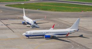 Two airplanes taxiing at the airport, on the steering track, and the gangplank. Stock Image