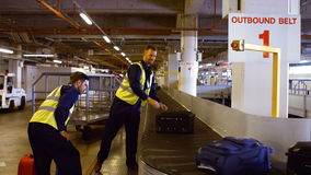 Two airport workers putting baggage on baggage carousel. At airport stock video footage