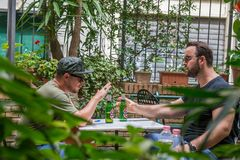 Two albanian mafia guys are smoking and drinking. Two albanian guys are dressed with a green and black t-shirt and blue jeans, green hat and black sunglasses royalty free stock images