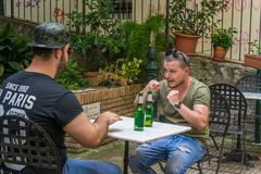Two albanian mafia guys are talking about fighting someone. Two albanian guys are dressed with a green and black t-shirt and blue jeans, green hat and black royalty free stock photos