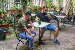Two albanian mafia guys are smoking and drinking. Two albanian guys are dressed with a green and black t-shirt and blue jeans, green hat and black sunglasses stock photos